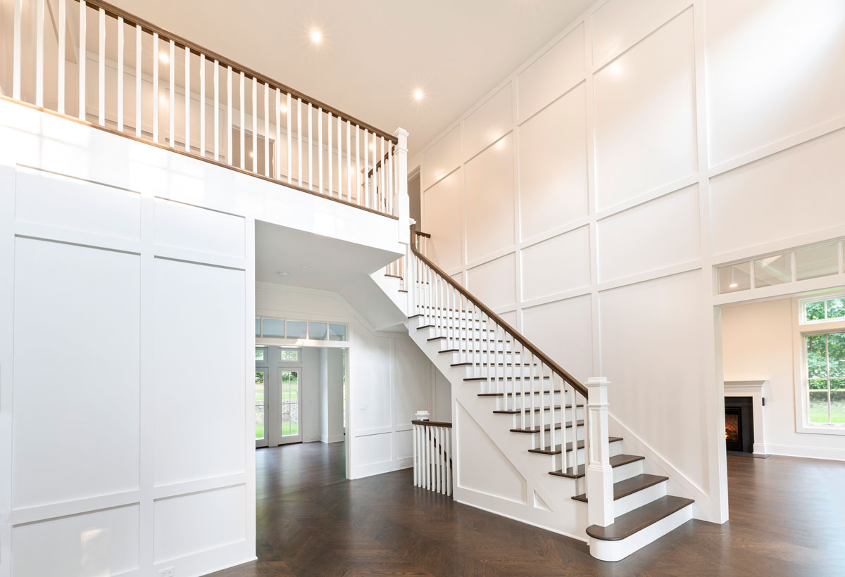 Long Island Architect Design Custom Entry and Stairwell with White Paneled Walls